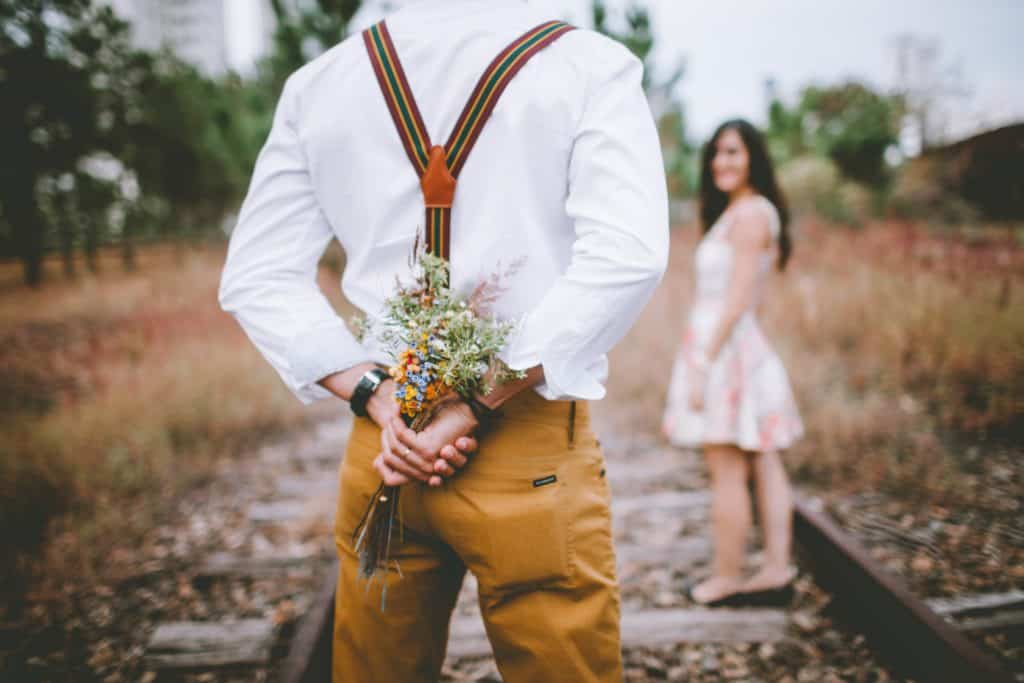 How to make someone fall in love with you. Man with flowers behind his back for his lady friend.