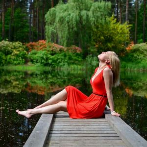 woman in red dress enjoying nature next to a river