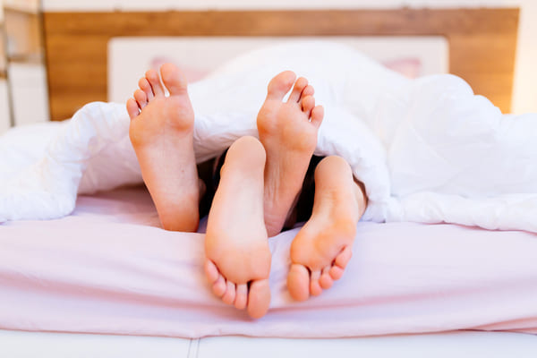 couple in bed with feet sticking out bottom of sheets