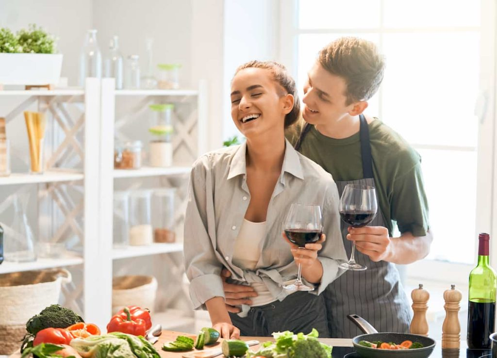 happy loving couple cooking together in kitchen