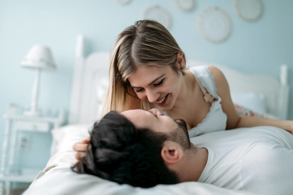couple lying in bed while having fun