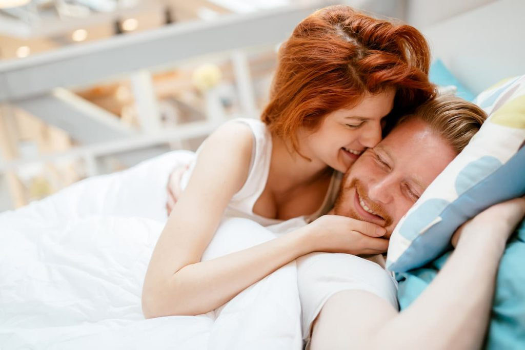 couple laughing while lying in bed