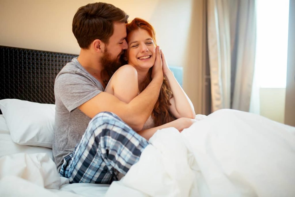 Sensual couple in bed being romantic