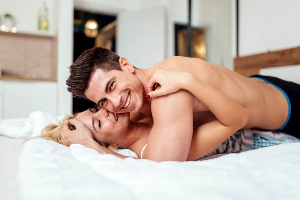 Handsome couple in bed being sensual