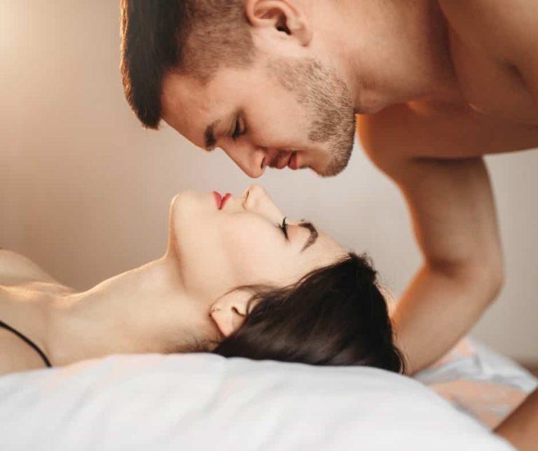 Love couple lies on big white bed, sex romance