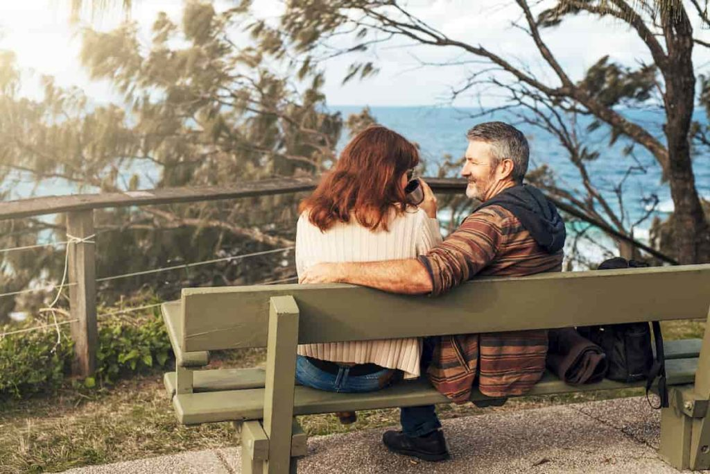Middle-aged couple sitting on the bench in park talking and hugging