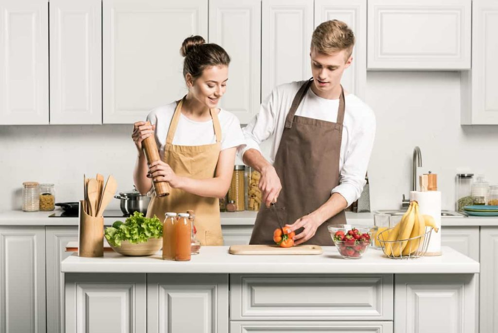 couple cooking salad and cutting vegetables in kitchen