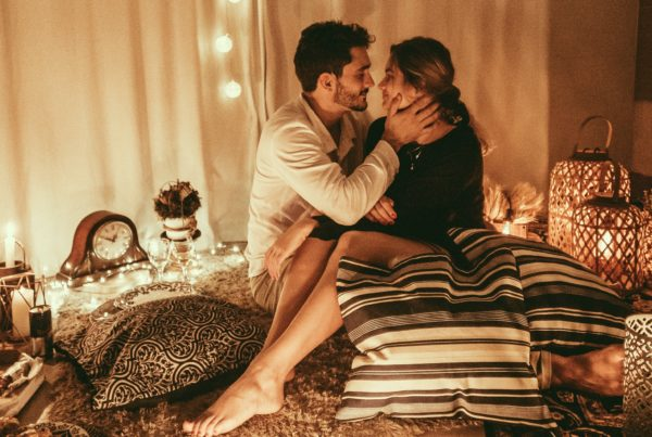 Capricorn-Man-and-Scorpio-Woman: couple about to kiss, sitting in bed