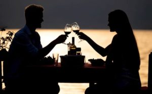 Capricorn-Man-with-Capricorn-Woman: couple enjoying a drink over dinner outdoors