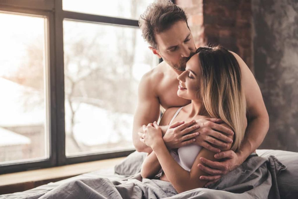Man is kissing his girlfriend and hugging in bed at home