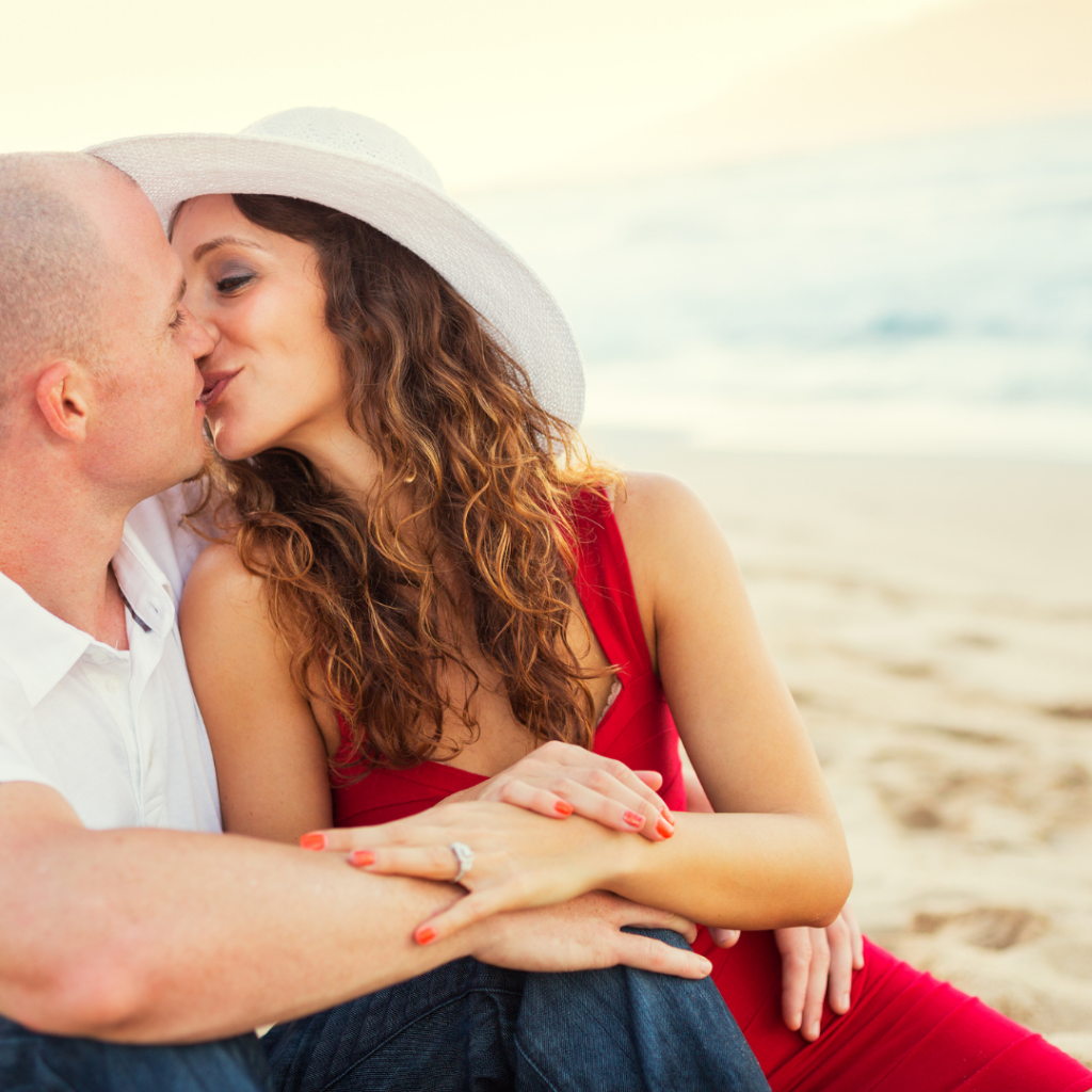 Happy couple in love, kissing enjoying sunset at the beach