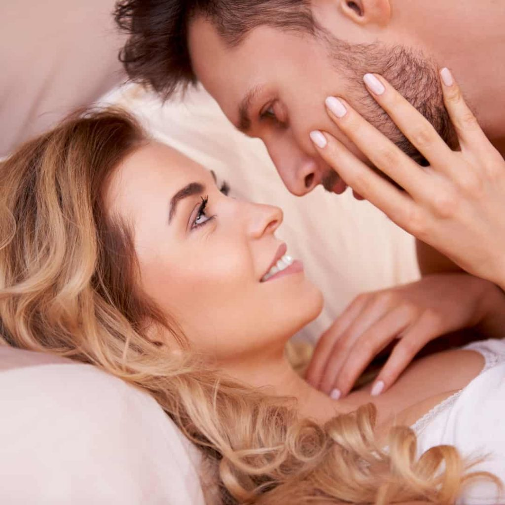 couple looking at each other while laying in bed