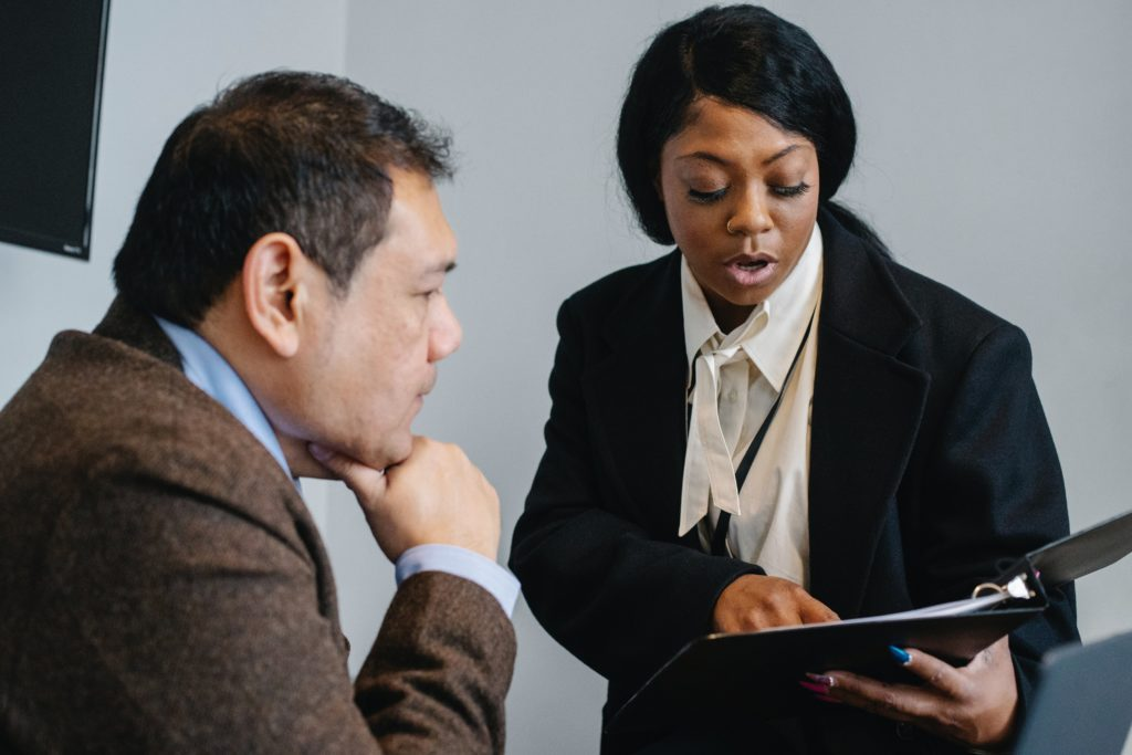woman explaining something to man in office