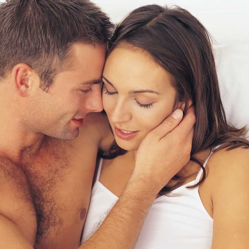 couple in bed touching each other