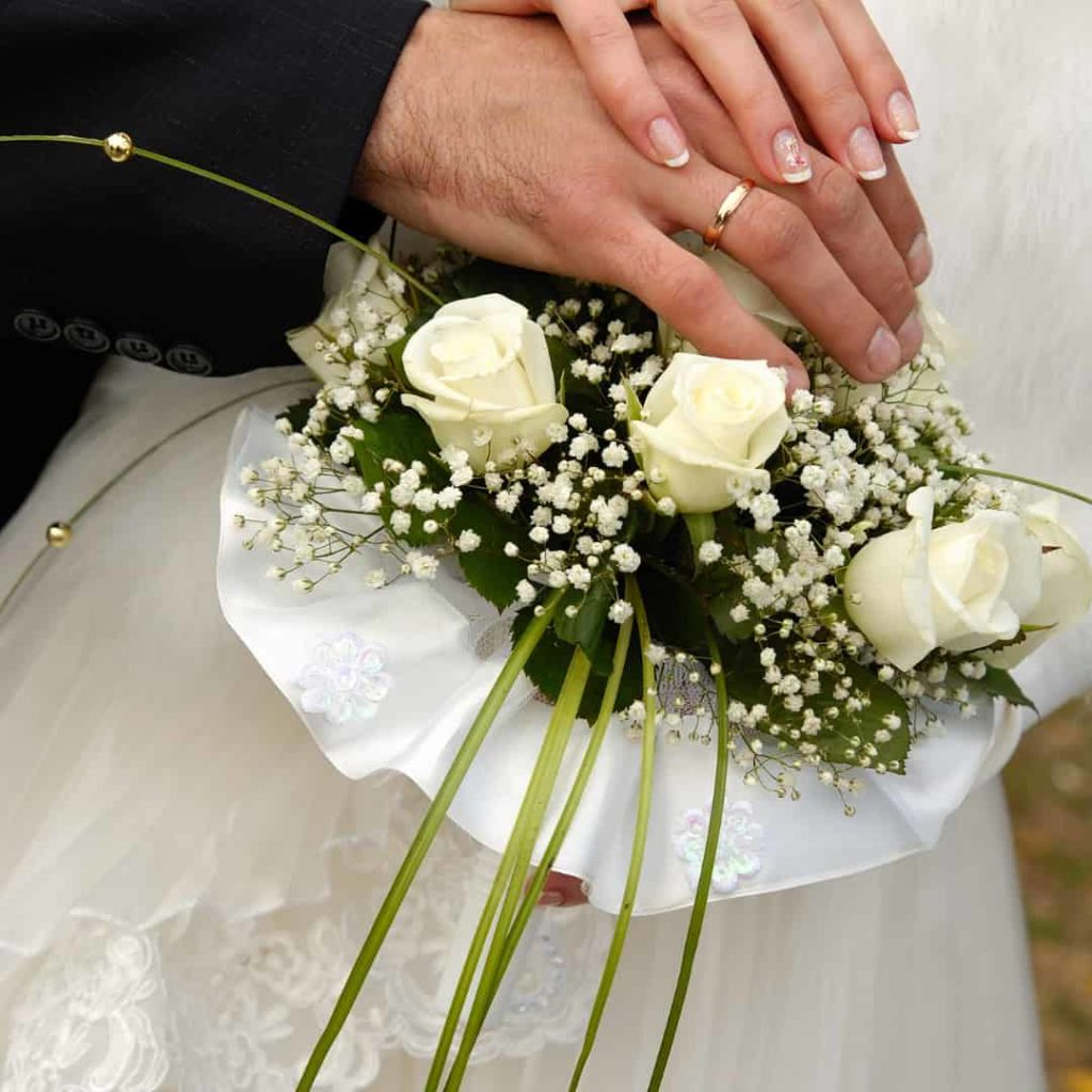 woman in suit and woman in wedding dress holding hands