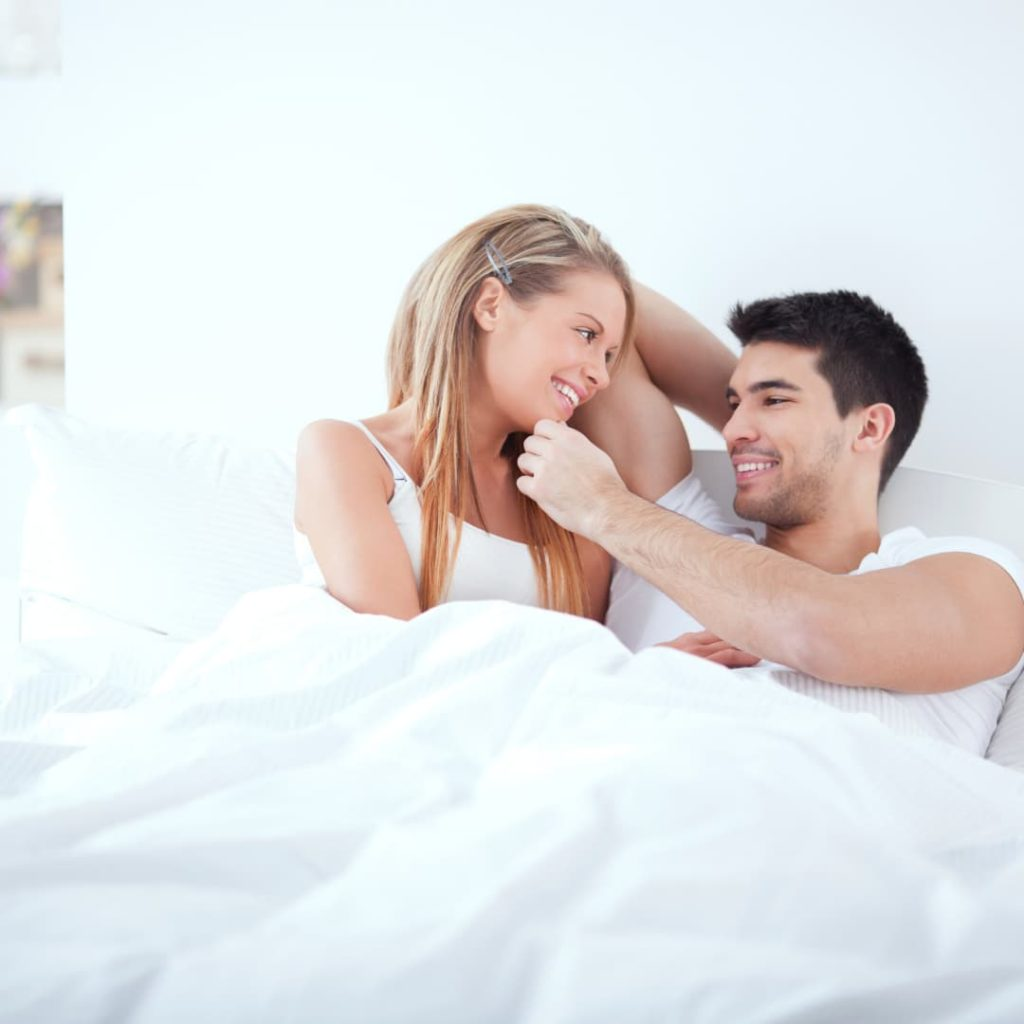 couple laying in bed ,touching and smiling together