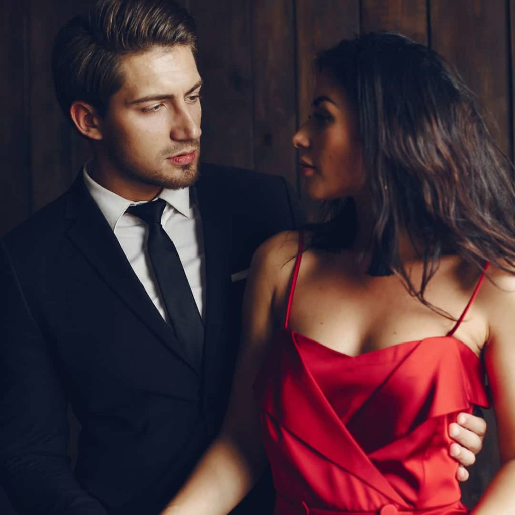 Elegant man and hot woman in a red dress looking at each other