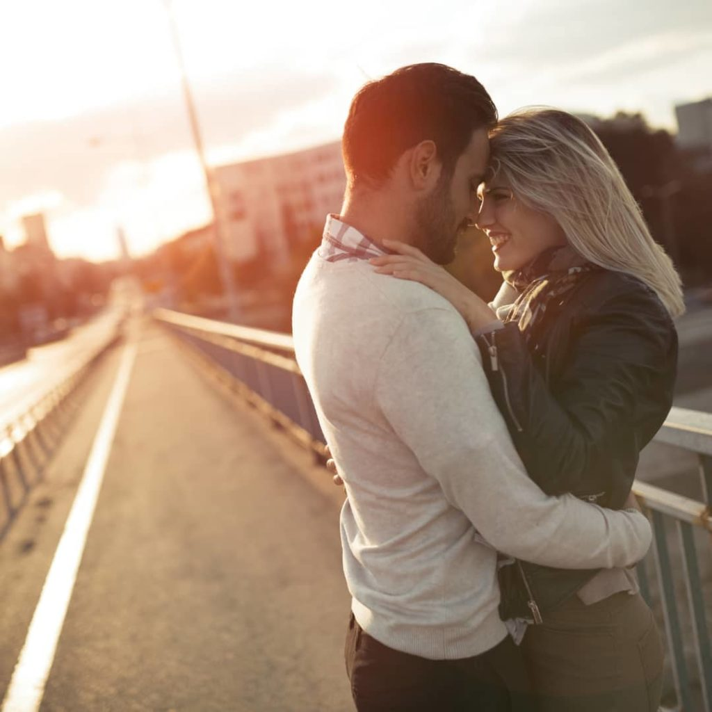Romantic couple in love enjoying sunset and kissing in a bridge