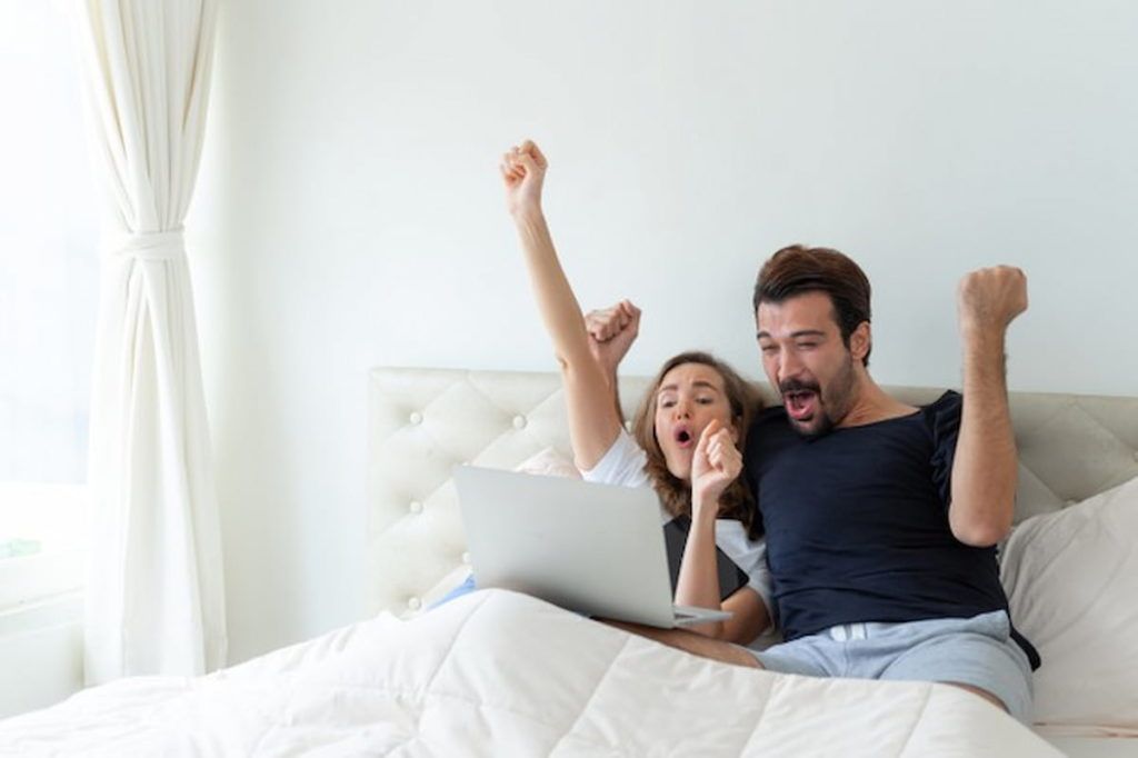 happy husband and wife watching football in laptop