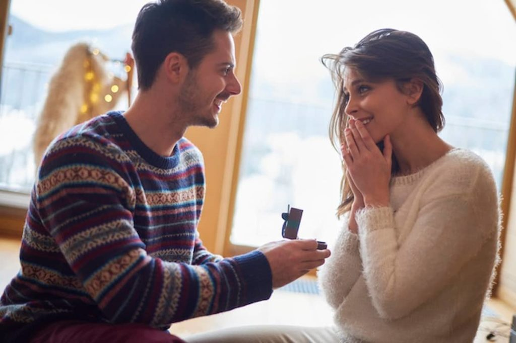 boyfriend proposing to his surprised girlfriend with a weeding ring