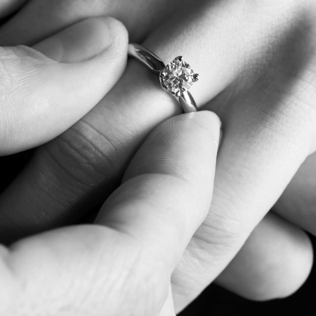male hand fitting diamond ring on fiance's hand after engagement proposal.