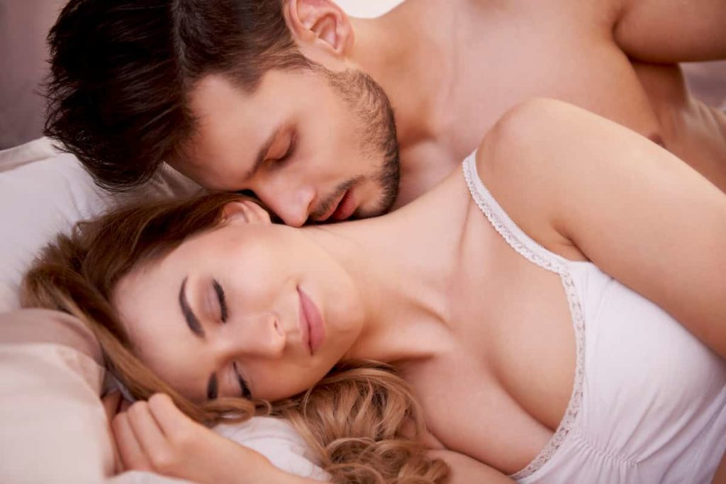 man kissing woman in neck while lying in bed