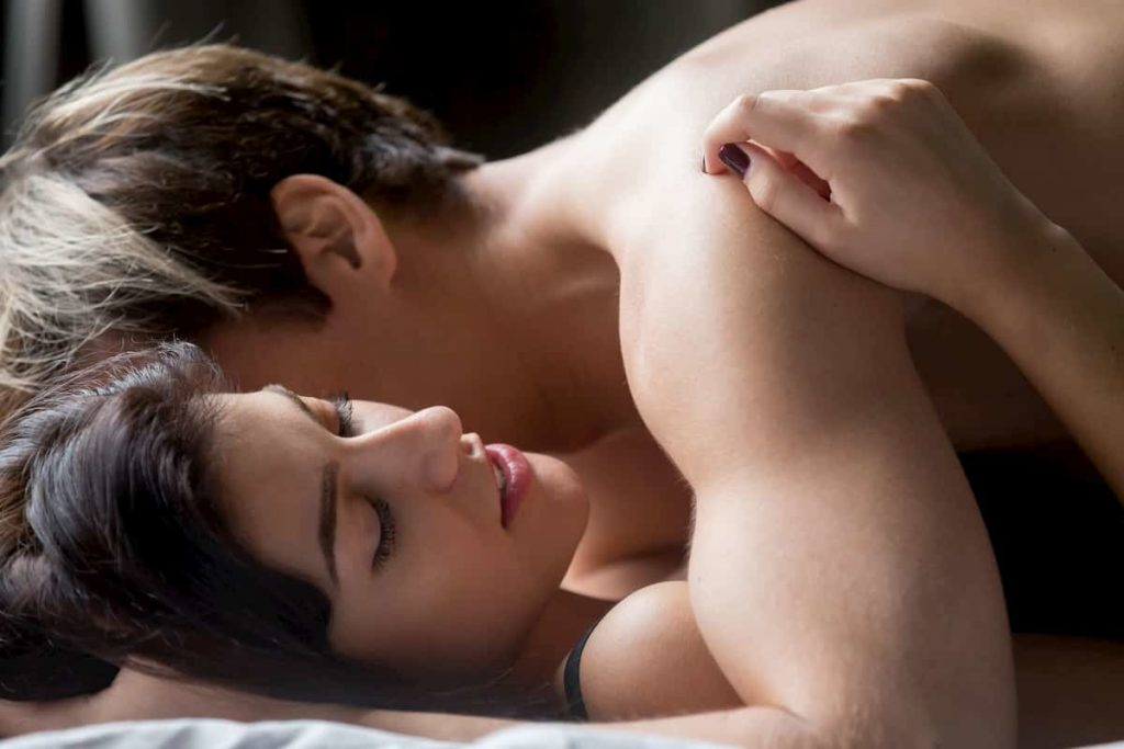 sensual couple having sex woman embracing lver lying in bed