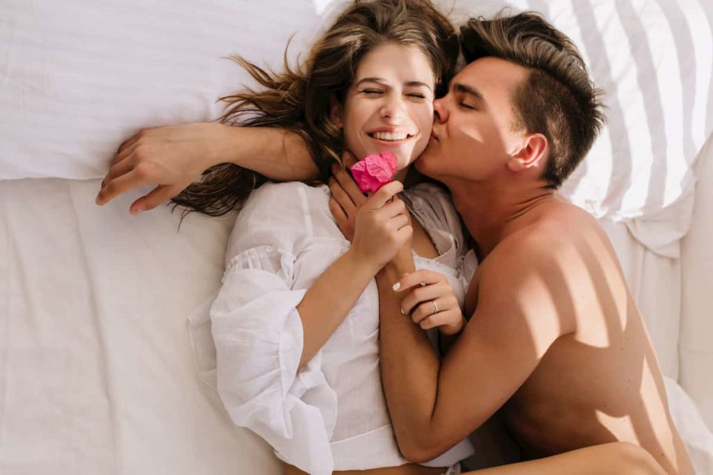 young woman holding pink flower and enjoying her boyfriend kisses
