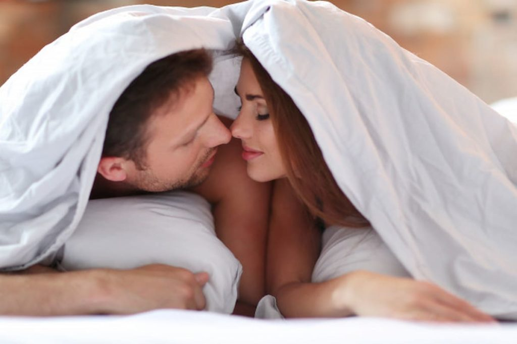 couple kissing under sheets