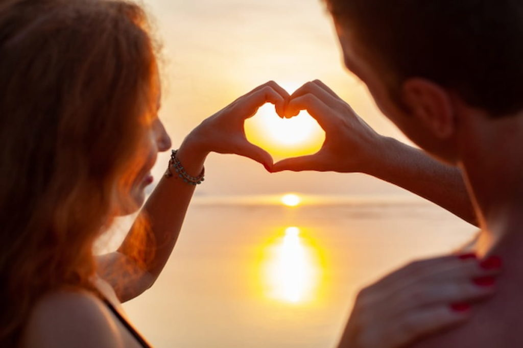 romantic couple showing heart sign at the beach