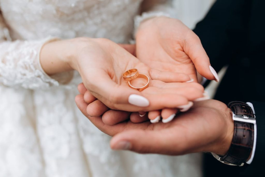 groom holds bride's hands with two wedding rings