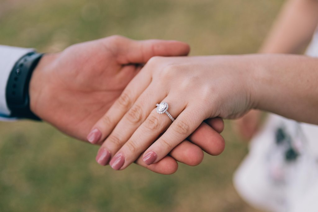 Virgo-Man-with-Scorpio-woman: man holding woman's hand after engagement
