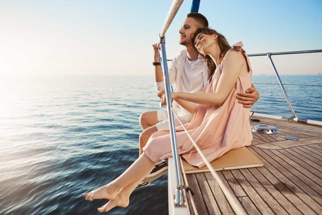 couple sitting on side of yacht watching at seaside and hugging