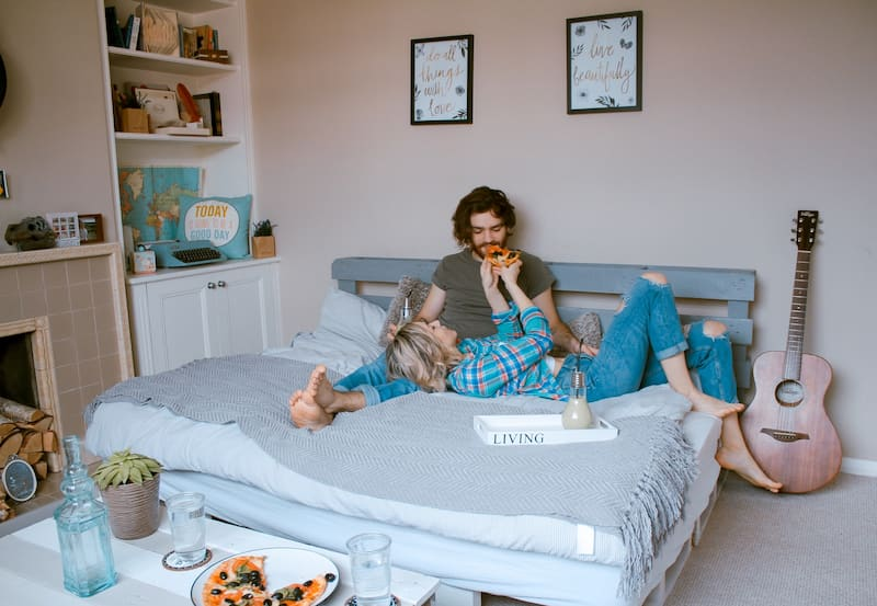 couple in bed eating pizza