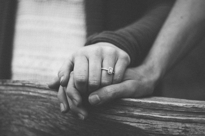 woman with a wedding ring holdin her man's hand