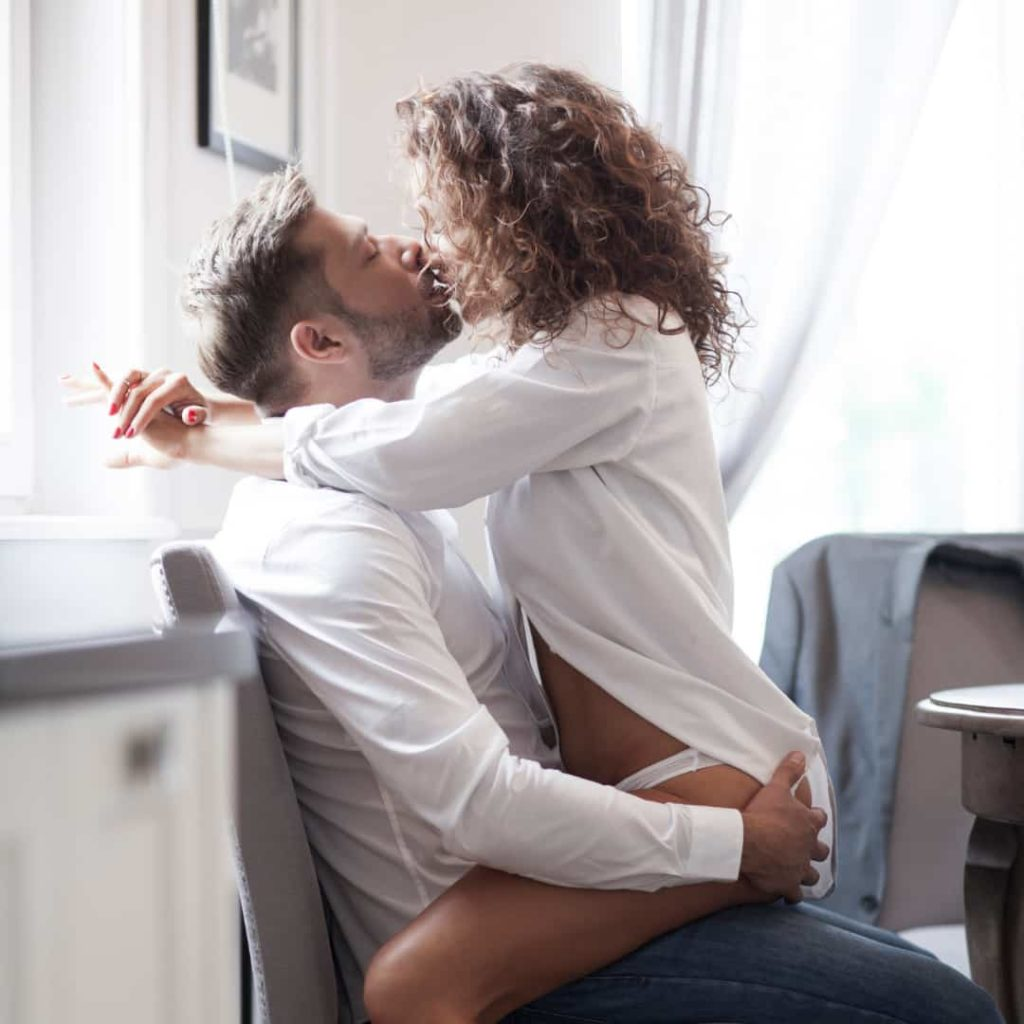 woman sitting on man in the kitchen