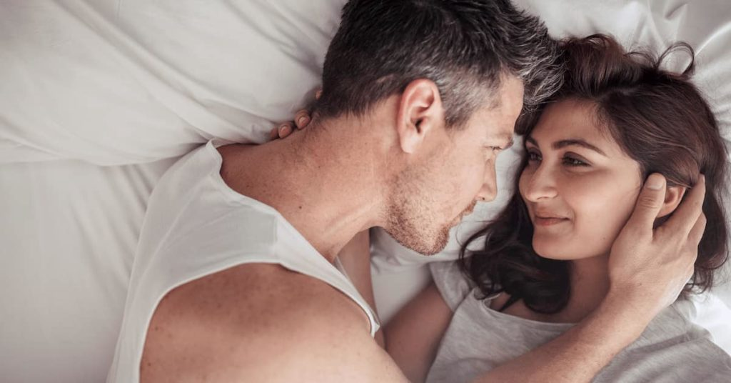 Overhead close up of young couple lying in bed together