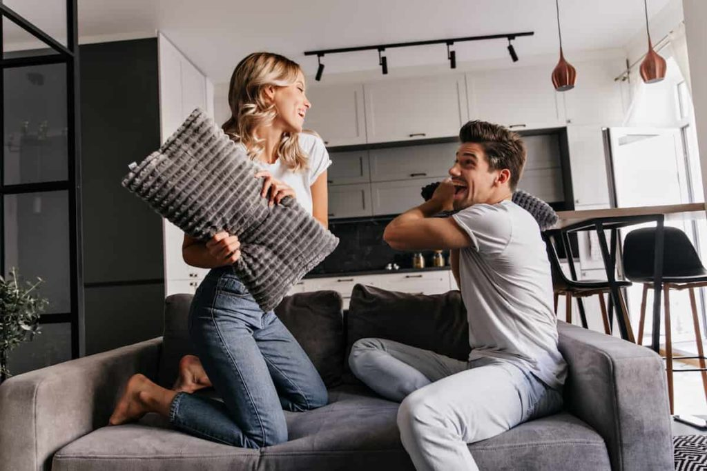 Scorpio Man and Aries Woman playing with pillows and laughing
