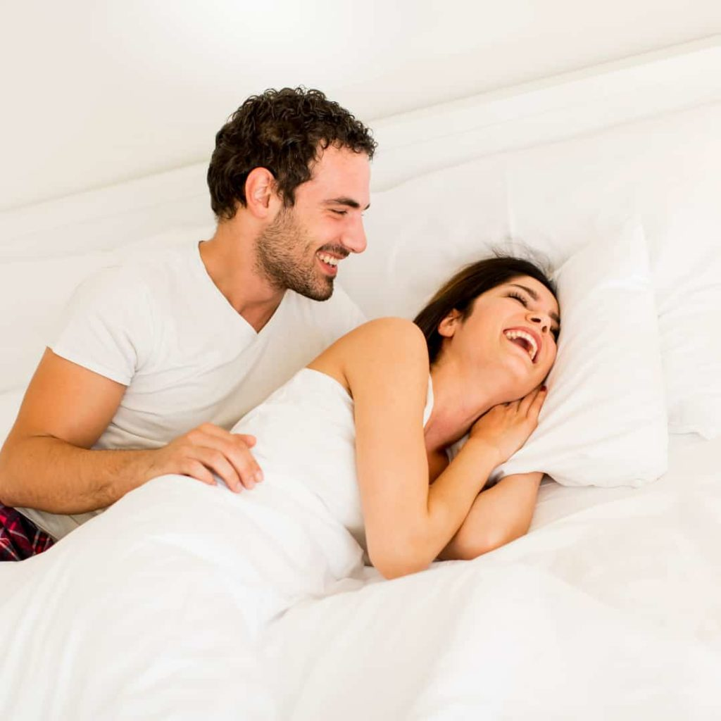 young couple laughing while laying in bed