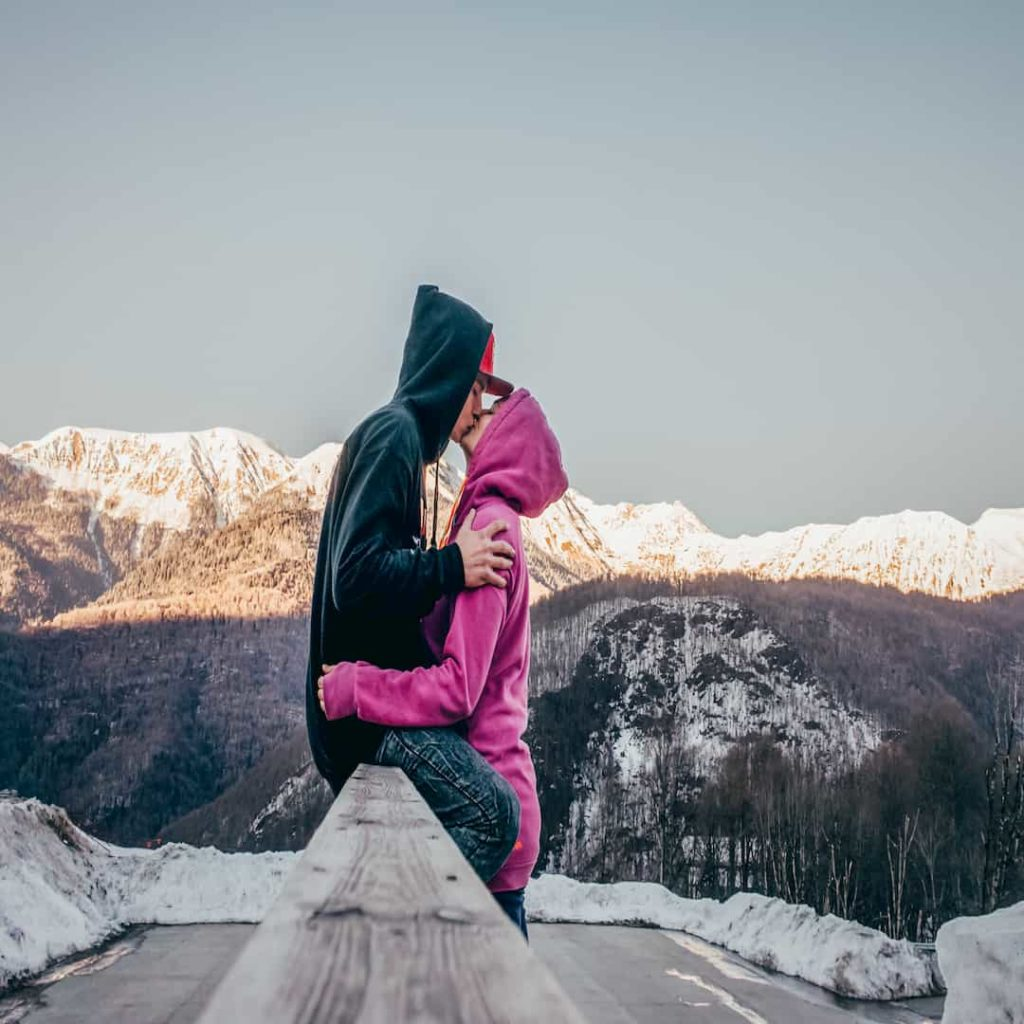 A couple in love kissing on the background of snow-capped mountain peaks