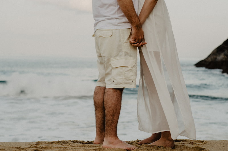 couple holding hands next to the sea