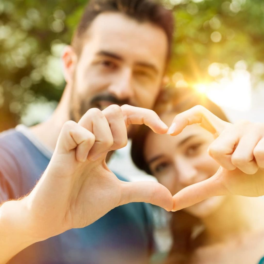 young man and woman making heart shape with hand