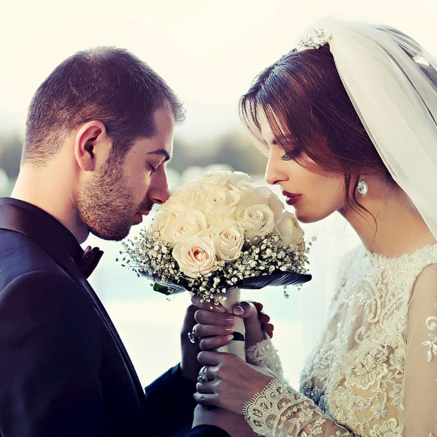 couple smelling bouqet while getting married