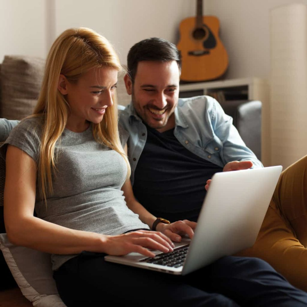 couple smiling and working in a laptop