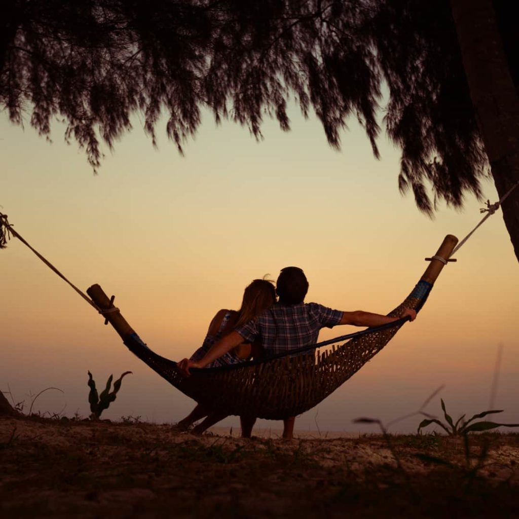Taurus man with Virgo woman: Young couple relaxing on a hammock at sunset