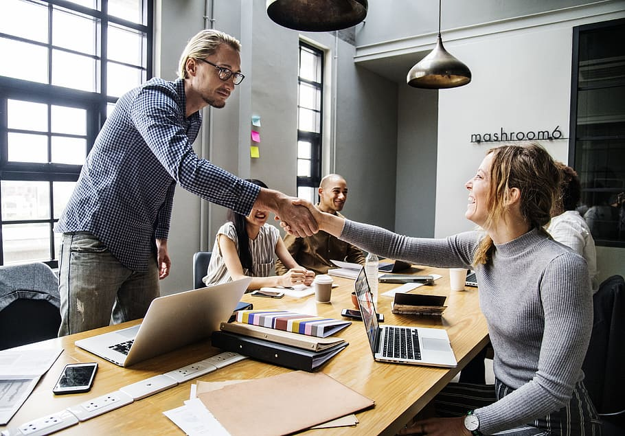 couple shaking hands in office happily
