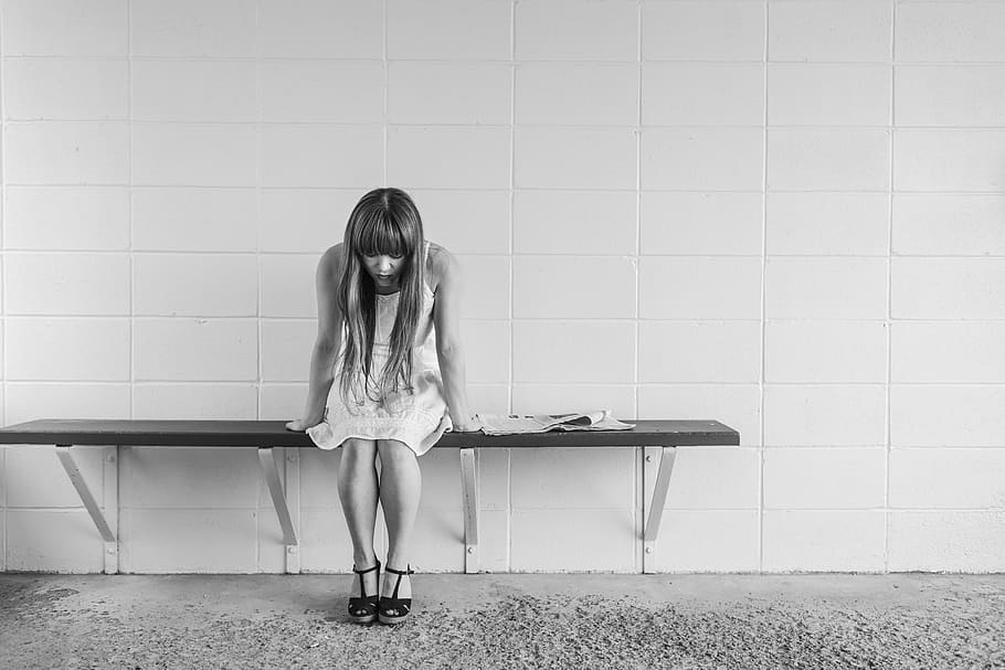 breakup guidance: girl sitting on bench with head down after a breakup