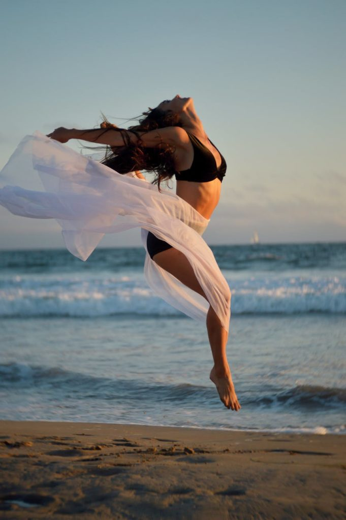 woman jumping with joy on a beach